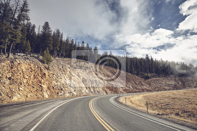 Mountain road bend in Yellowstone National Park, color toning applied, USA.