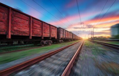Moving freight train at sunset. Railroad and beautiful sky with clouds with motion blur effect in summer. Industrial landscape with train, railway station and blurred background.  Railway platform