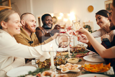 Obraz Multi-ethnic group of people raising glasses sitting at beautiful dinner table celebrating Christmas with friends and family, copy space