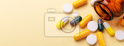 Obraz Multicolor tablets and pills capsules from glass bottle on yellow background Health care Close-up Horizontal banner Copy space