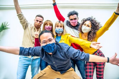 Obraz Multicultural people covered by protective face masks smiling at camera - New normal friendship concept with young friends having fun outdoor - Bright filter