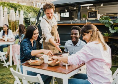 Obraz Multiracial people having fun eating at food truck outdoor - Focus on left girl face