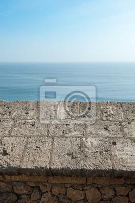 mur z morzem i niebieskim tle nieba.