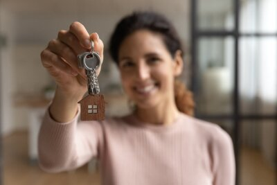 Obraz My most successful investment. Portrait of young hispanic female happy homeowner look at camera celebrate moving to new house apartment closing deal getting mortgage. Soft focus on hand showing keys