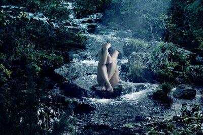 Obraz Naga dziewczyna siedzi na skałach górskiej rzeki w nocy.