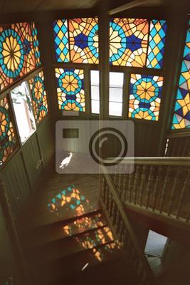 Obraz Nasycone kolory witraży odzwierciedlenie na schodach starego domu mieszkalnego w Tbilisi, Gruzja. Głębokie cienie i jasne światło wpadające przez okna. Fotografia kinowa.