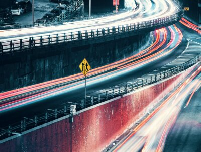New York City street at night with cars light trails, color toned long exposure picture, USA.