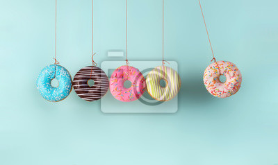Obraz Newton's cradle from doughnuts. Collision balls made from donuts. Harm of sugar, donuts time or healthy diet concept. Dependence on flavoring, diabetes problems, weight loss.