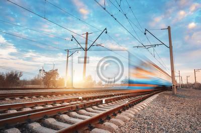 Niebieski pociąg pasażerski dużych prędkości w ruchu na kolei na zachodzie słońca. Niewyraźny pociąg pasażerski. Dworzec kolejowy przeciwko kolorowe niebo. Turystyka kolejowa, turystyka kolejowa. Kraj