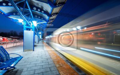 Niewyraźne szybki pociąg na stacji kolejowej w nocy w Europie. Krajobraz miejski z nowoczesnym pociągiem pasażerskim w ruchu na peronie kolejowym z oświetleniem. Pojazd międzymiastowy. Podróż koleją