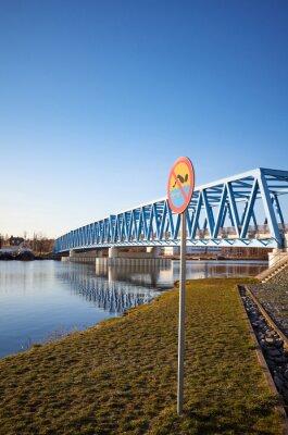 No swimming sign by Odra River in Szczecin sunset, Brdowski Bridge in background, Poland.