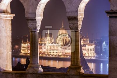 Nocny widok na budynek parlamentu węgierskiego między kolumnami twierdzy i punktu widzenia Basztę Rybacką, położonych nad brzegiem Budy