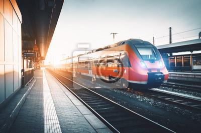 Nowoczesna high speed red pociągów podmiejskich na stacji kolejowej na zachód słońca. Włączenie reflektorów kolejowych. Kolej z rocznika tonowania. Pociąg na peronie. Przemysłowy krajobraz. turystyka
