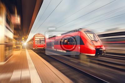 Nowoczesna wysoka prędkość pociągów pasażerskich czerwone o zachodzie słońca. Stacja kolejowa w Norymberdze, Niemcy. Kolej z efektu rozmycia ruchu. Koncepcja Przemysłowy krajobraz