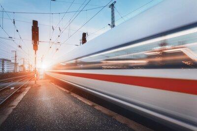 Nowoczesna wysoka prędkość pociągu pasażerskiego na kolei w ruchu na zachód słońca. Niewyraźne pociągów podmiejskich. Dworzec kolejowy o zmierzchu z rocznika tonowania. tło Podróże, turystyka kolejowa