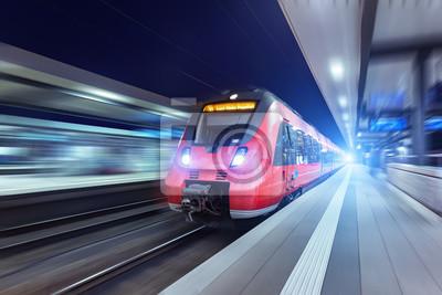 Nowoczesne szybki czerwony pociąg pasażerski w nocy