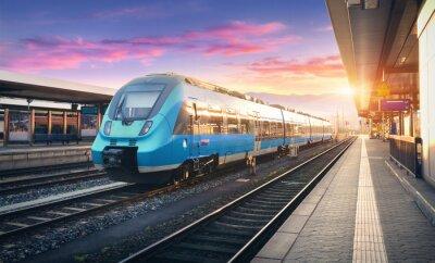 Nowoczesny szybki pociąg podmiejski na dworcu kolejowym i kolorowe niebo z chmurami o zachodzie słońca w Europie. Krajobraz przemysłowy z niebieskim pociągiem pasażerskim na platformie kolejowej. Tło