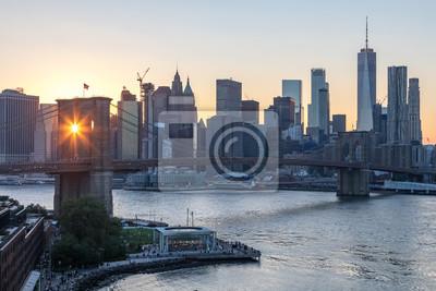 Nowy Jork - promienie słońca świecą przez łuki mostu Brooklyn Bridge z panoramą centrum Manhattanu w tle