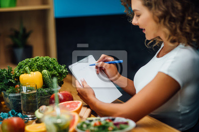Obraz Nutritionist working in office. Doctor writing diet plan on table and using vegetables. Sport trainer.