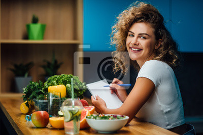 Obraz Nutritionist working in office. Doctor writing diet plan on table and using vegetables. Sport trainer. Lifestyle.