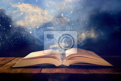 Obraz obraz otwartej książki antyczne na drewnianym stole z nakładką świecidełka.
