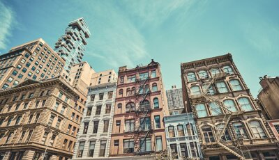 Old buildings with fire escapes, color toning applied, New York City, USA.