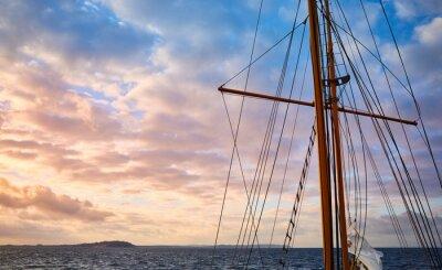 Old sailing ship mast at beautiful sunrise, travel concept.