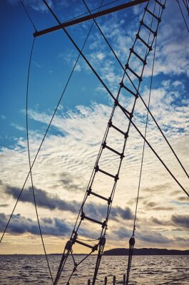Old schooner rope ladder and rigging silhouette at sunset, color toning applied.