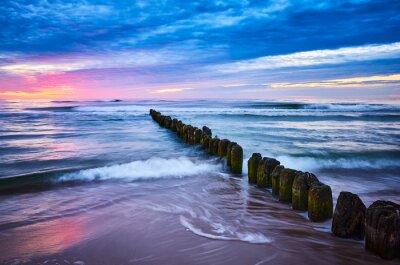 Old wooden breakwater at purple sunset, Baltic Sea coast in Mrzezyno, Poland.