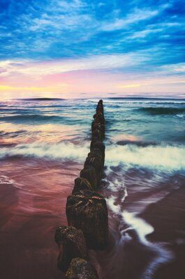 Old wooden breakwater at purple sunset, color toned picture.