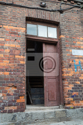 Old wooden door in red brick house