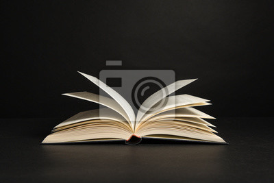Obraz Open book with pages on a black background