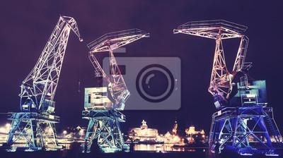Oświetlone stare żurawie portowe na bulwarze w Szczecinie w nocy, zastosowanie tonacji kolorystycznej, Polska.