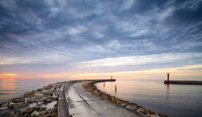 Panoramic view of rocky pier at the entrance to the harbor at sunset.