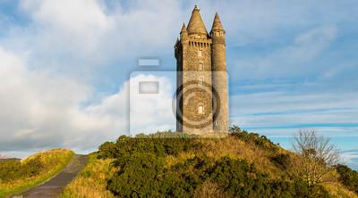Obraz Panoramiczny widok ścieżki prowadzącej do starej wieży zamku na szczycie wzgórza pod błękitne niebo z białymi bufiastymi chmurami