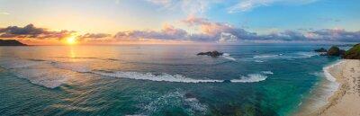 Obraz Panoramiczny widok tropikalna plaża z surfingowami przy zmierzchem.