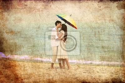 Para całuje pod parasolem na plaży