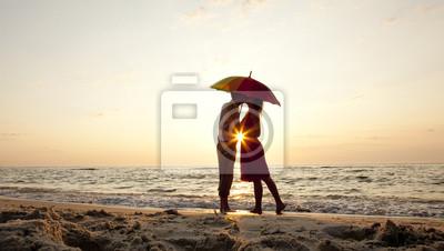 Para całuje pod parasolem na plaży w zachodzie słońca.