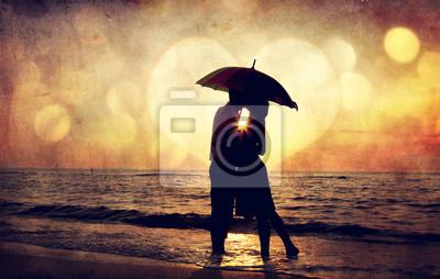 Para całuje pod parasolem na plaży w zachodzie słońca. Zdjęcia w o.
