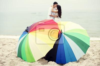Para całuje się na plaży i parasol