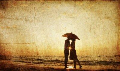 Obraz Para całuje się na plaży w słońca.