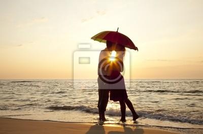 Para całuje się na plaży w słońca.