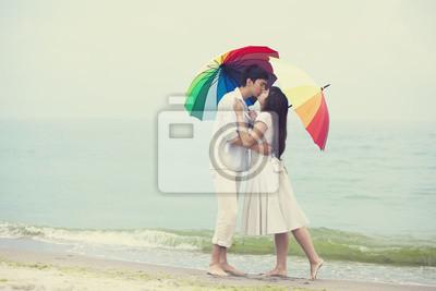Para całuje się na plaży z parasolem
