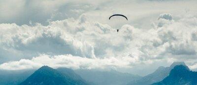 Obraz Paralotnia w górach i pochmurne niebo w tle