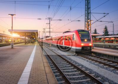 Pasażerski wysoki prędkość pociąg na staci kolejowej przy zmierzchem. Krajobraz miejski z nowoczesną pociągiem podmiejskim na peronie kolejowym z oświetleniem o zmierzchu. Intercity pojazdu na linii k