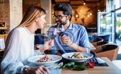 Obraz Paste and red wine. Young couple enjoying lunch in the restaurant. Lifestyle, love, relationships, food concept