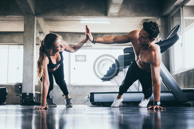 Obraz Personal trainer helping woman exercising in the sport gym