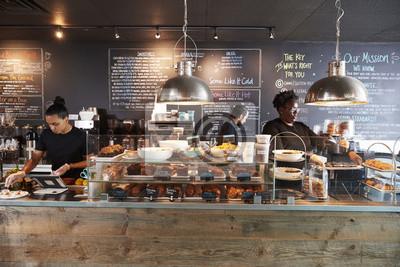 Obraz Personel pracuje za kontuarem w zajęty sklep z kawą