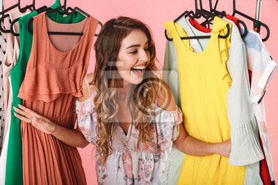 Obraz Photo of attractive woman in dress standing inside wardrobe rack full of clothes