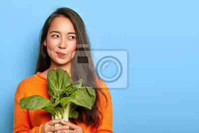 Obraz Photo of attractive young woman holds fresh green vegetable, eats healthy food at home, uses food product for making vegetarian salad, wears orange jumper, poses indoor. Home growing concept.
